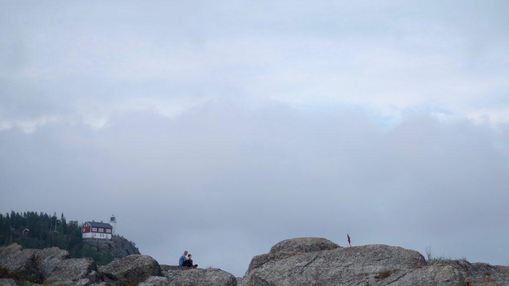 Två personer samtalar på en klippa på Högbonden med fyren i bakgrunden.
